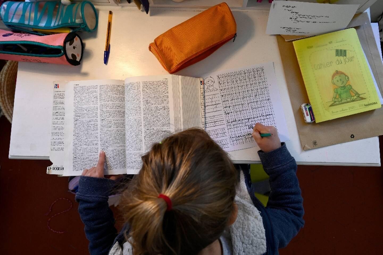 Une fillette fait ses devoirs le 6 avril 2021 à Marseille alors que les écoles sont fermées en raison de la crise sanitaire