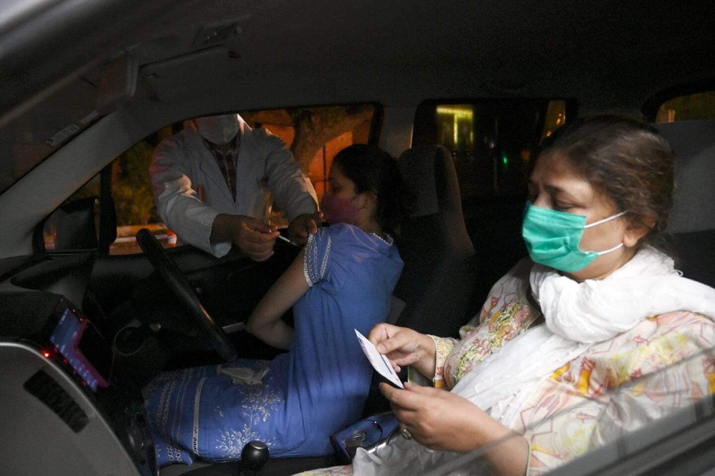 Une femme reçoit le vaccin chinois Sinopharm contre le Covid-19 à bord de sa voiture, à Lahore, au Pakistan, le 10 juin 2021