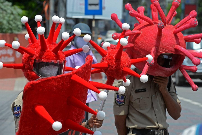 Des policiers portant des déguisements sur le thème du coronavirus, pour inciter les habitants à respecter les restrictions sanitaires, sont postés à un carrefour de Hyderabad (Inde), le 27 mai 2021