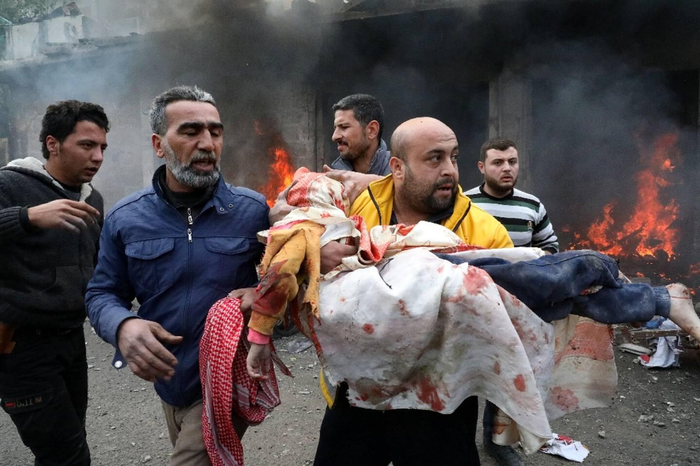 Des civils portent une jeune victime après une explosion dans la ville d'Azaz sous contrôle rebelle dans le nord de la Syrie le 31 janvier 2021.