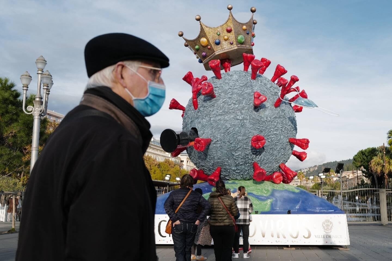 Un homme portant un masque passe près d'une sculpture à l'effigie du virus créée par des caravaliers à Nice, le 16 février 2021