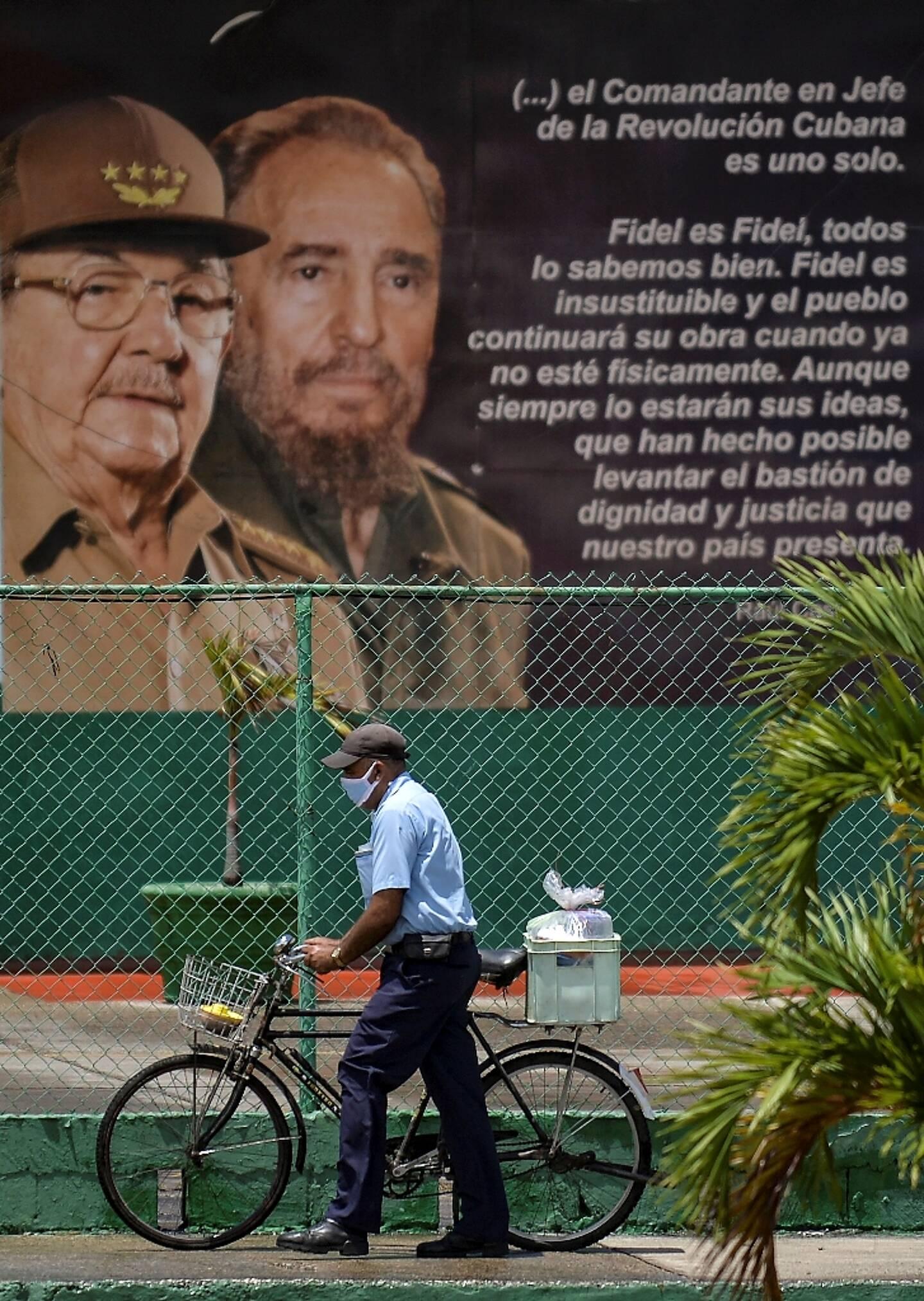 Un homme passe devant une affiche montrant les ex-présidents cubains Fidel et Raul Castro, à La Havane le 13 avril 2021