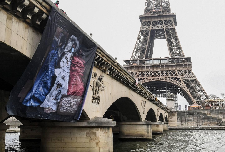 """Une banderole représentant le drapeau français et portant l'inscription """"durant l'épidémie, une autre tragédie se produit. Des milliers de SDF ont besoin de nous"""", accrochée sur le pont Iena à Paris le 16 décembre 2020"""