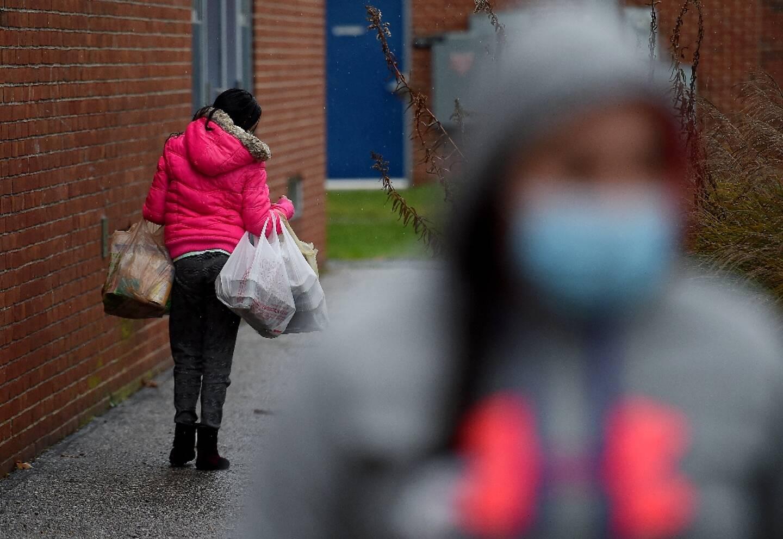 Une personne porte de la nourriture récupérée auprès d'un centre de charité, à Baltimore, le 4 décembre 2020