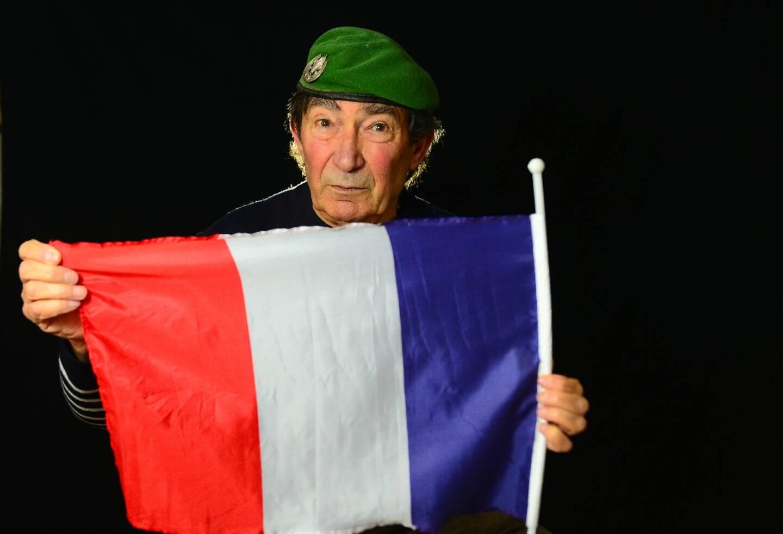 Le vétéran Régis Guillem, ancien membre de l'OAS, béret sur la tête, tient le drapeau français, le 5 février 2021 chez lui, à Royan
