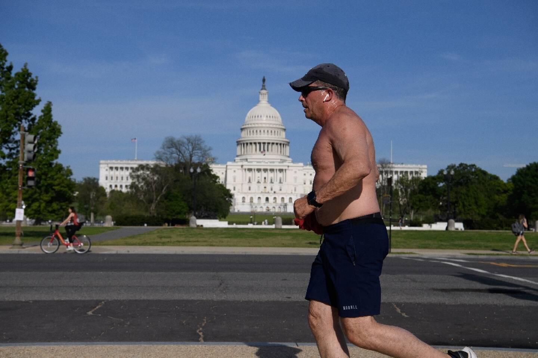 Aux Etats-Unis, les personnes vaccinées n'ont plus besoin de porter de masque lorsqu'elles sont en extérieur, mis à part lorsqu'elles se trouvent dans des foules. Un joggeur sans masque passe devant le Capitole, à Washington DC, le 27 avril 2021