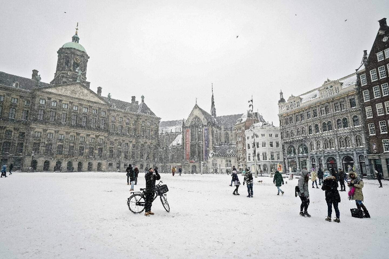 Des piétons traversent la place du Dam couverte de neige, le 7 février 2021 à Amsterdam