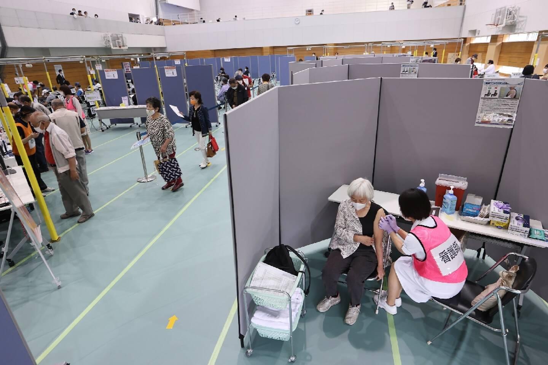 Une femme se fait vacciner alors que d'autres personnes font la queue dans un nouveau centre de vaccination, ouvert le 24 mai 2021 à Toyoake City dans la préfecture d'Aichi (Japon)