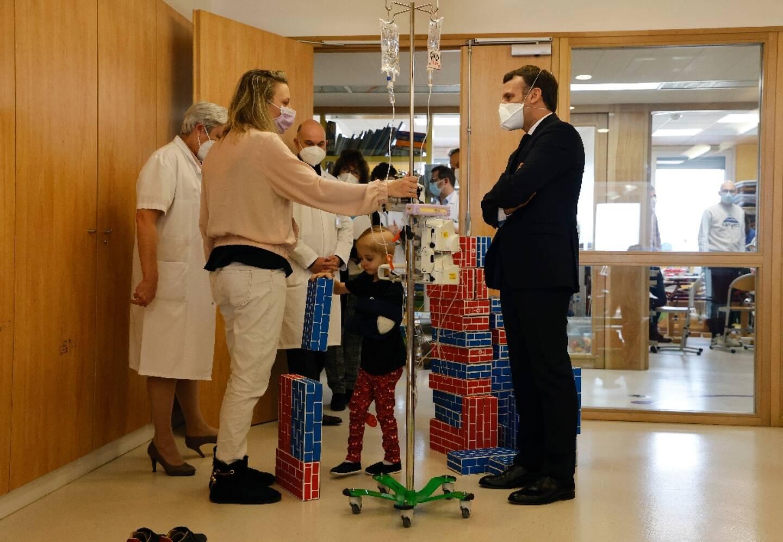 Le président Emmanuel Le président Emmanuel Macron discute avec une mère à l'unité pédiatrique de l'institut Gustave-Roussy à Villejuif le 4 février 2021