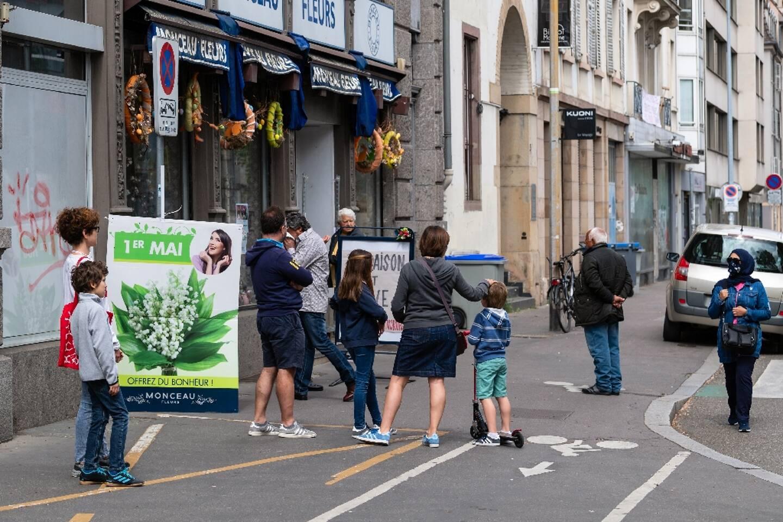 Des clients attendent devant un magasin de fleurs pour acheter du muguet, le 1er mai 2020 à Strasbourg