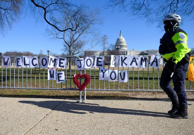 un policier passe devant une banderole souhaitant la bienvenue à la future vice-président Kamala Harris près du Capitole le 10 janvier 2021