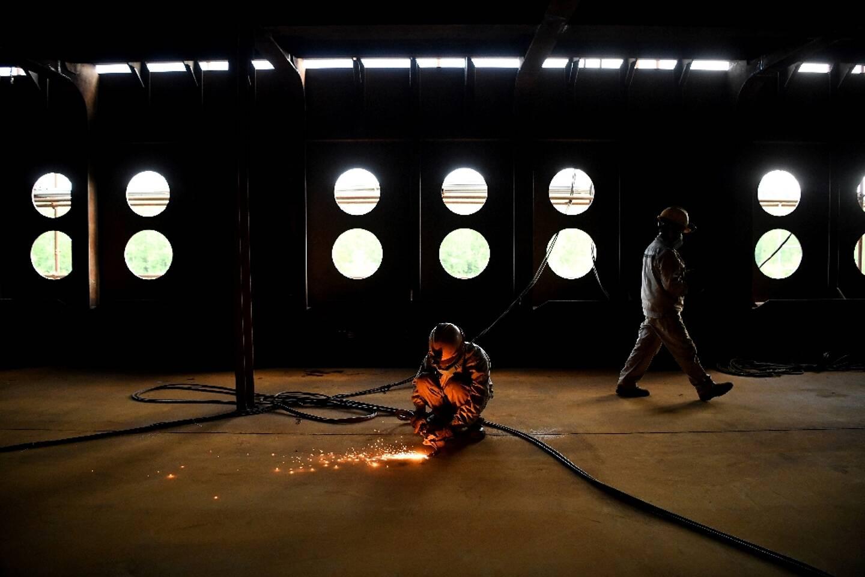 Un ouvrier effectue une soudure, sur le chantier d'une réplique du Titanic, le 27 avril 2021, dans le district de Daying (Chine)