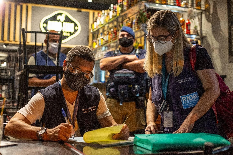 Des agents sanitaires imposent une amende à un gérant de restaurant pour non-respect des règles le 6 mars 2021 à Rio de Janeiro (Brésil)