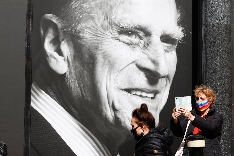 Deux passantes devant le portrait de feu le prince Philip, à Windsor (Royaume-Uni), le 16 avril 2021