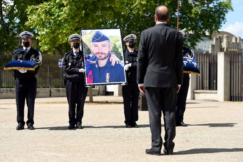 Le Premier ministre Jean Castex (D) devant le portrait du policier Eric Masson, tué à Avignon, lors d'un hommage national le 11 mai 2021 à Avignon