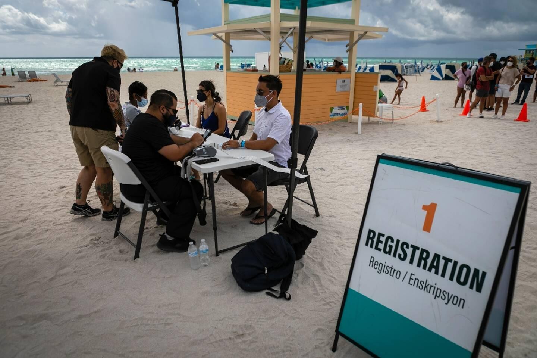 Des gens s'enregistrent pour se faire administer le vaccin Johnson & Johnson contre le Covid-19, dans un centre ouvert sur une plage à South Beach, en Floride, le 9 mai 2021