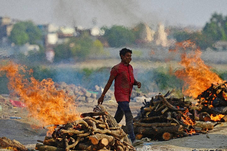 Un homme marche entre les bûchers d'un crématorium à Allahabad, en Inde, le 27 avril 2021