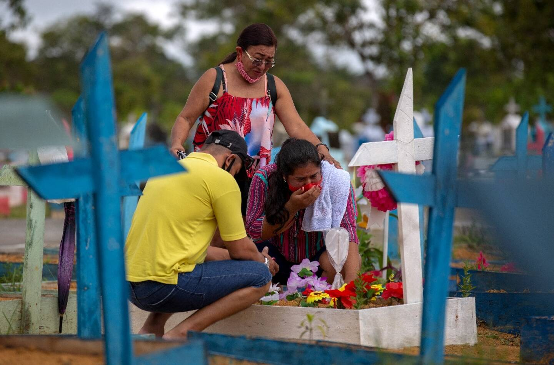 Des proches sur la tombe d'une personne décédée du Covid-19, à Manaus, au Brésil, le 9 mai 2021