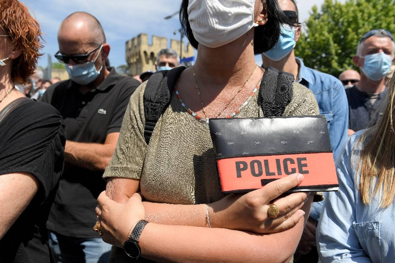 Une officier de police arbore son badge police le 9 mai 2021 à Avignon lors de l'hommage à son collègue tué