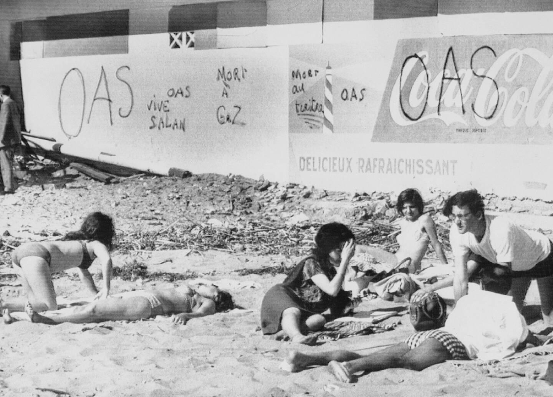 Des Algérois se détendent à la plage près d'Alger le 2 avril 1962, devant des graffiti favorables à l'OAS