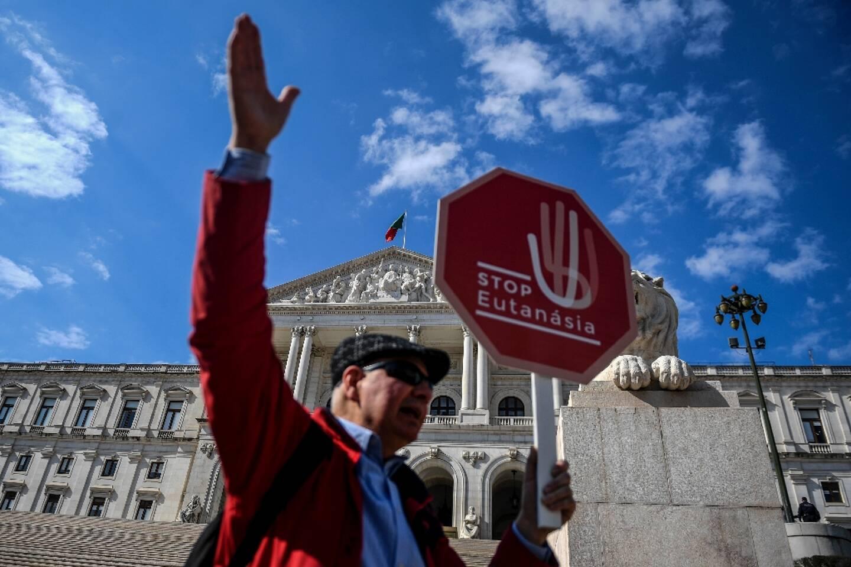"""Un homme tient une pancarte """"Stop à l'euthanasie"""" lors d'une manifestation devant le Parlement à Lisbonne, le 20 février 2020"""