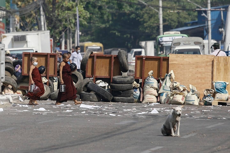 Des jeunes moines marchent devant une barricade montée par des manifestants contre le coup d'Etat militaire, à Rangoun (Birmanie), le 11 mars 2021.