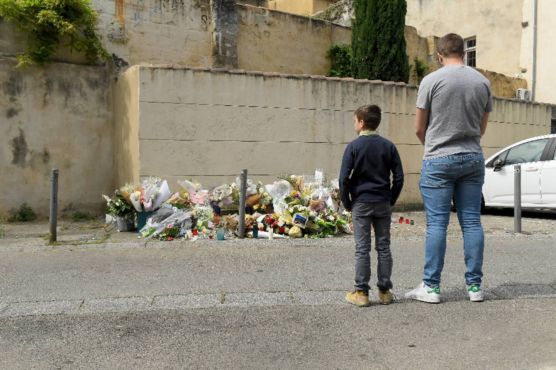 Un homme et son fils, le 9 mai 2021, devant le lieux où le policier a été tué à Avignon