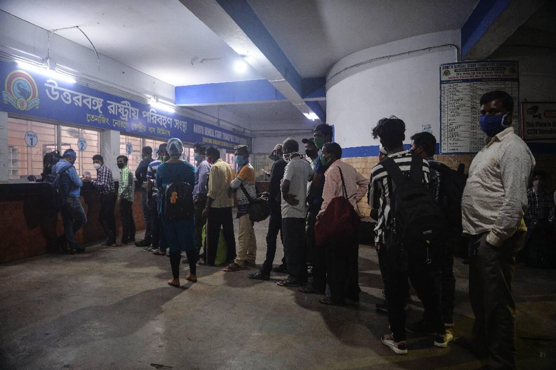 Des personnes font la queue pour acheter un billet d'autocar le 15 mai 2021 à Siliguri, en Inde, après que l'Etat du Bengale occidental a décrété un confinement de deux semaines pour freiner les contaminations