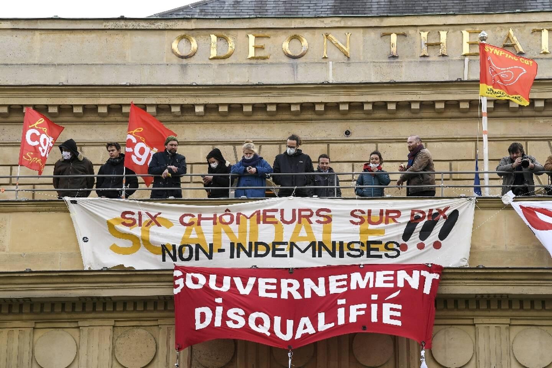Des manifestants de la CGT ont tendu une banderole sur la facade du théatre national de l'Odéon le 5 mars demandant la réouverture des lieux culturels un an après le début du premier confinement