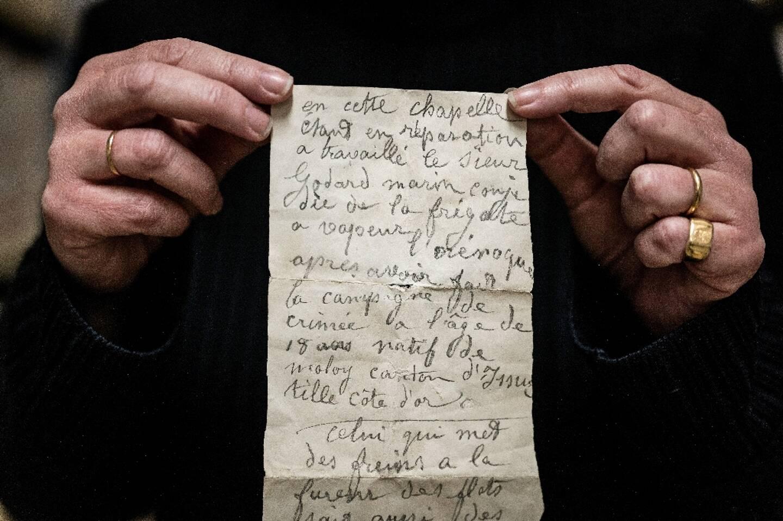Une employée des archives municipales de Dijon montre le 20 janvier 2021 un texte manuscrit de 1856 trouvé dans le mur d'une chapelle