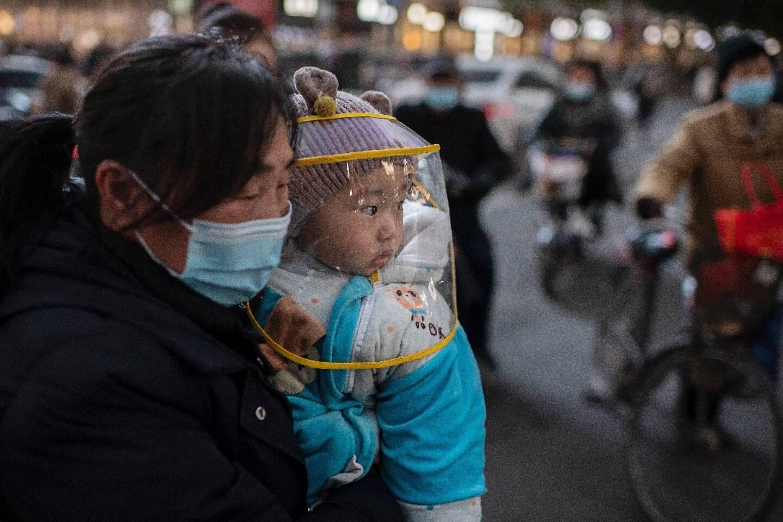 Une femme et son enfant près d'un centre commercial à Wuhan (Chine) le 13 janvier 2021