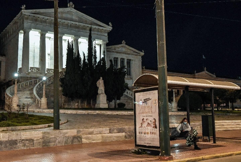 Une femme porte un masque de protection dans un arrêt de bus dans le centre d'Athènes, en Grèce, où le gouvernement a prolongé le confinement et durci les restrictions contre la pandémie, le 3 mars 2021