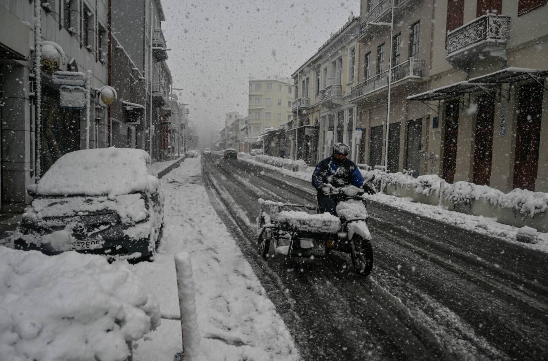 """Un homme conduit une moto dans le centre d'Athènes lors de chutes de neige d'une rare puissance le 16 février 2021. L'agence météorologique grecque a déclaré que """"les basses températures, la glace et les chutes de neige"""" se poursuivraient le 16 février, l'agence de protection civile recommandant aux gens d'éviter de voyager."""
