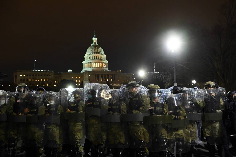 Les forces de police anti-émeute se préparent à disperser les supporters pro-Trump qui ont envahi le Capitole pour perturber une session du Congrès qui doit certifier la victoire de Joe Biden à l'élection présidentielle.