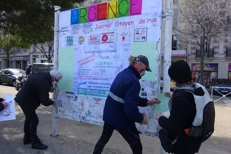 Devant le panneau d'expression libre de la gare routière, Guy Cochennec, coordonnateur de la démarche, Christine Flori, de la Ligue des droits de l'Homme, et Guillaume, ancien de la SCNM, à leur pinceau.