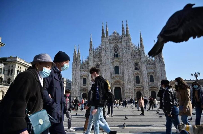 Des piétons portant des masques de protection passent devant le Duomo, la cathédrale de Milan, le 17 octobre 2020.