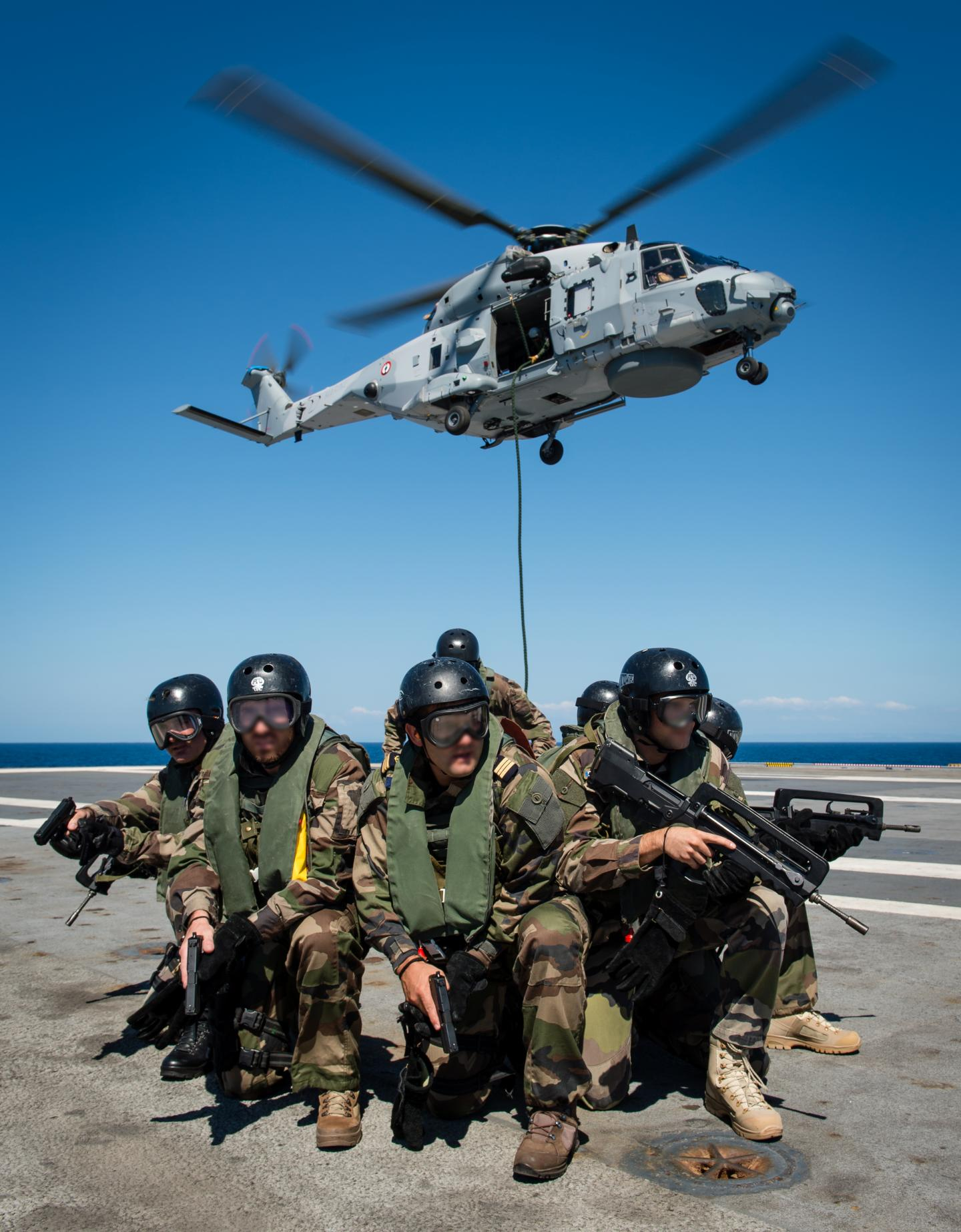 """Sur le pont d'envol du Charles-de-Gaulle, une équipe de l'unité de fusiliers marins (UNIFUSIL) effectue un entraînement corde lisse depuis un hélicoptère """"Caïman"""" marine (NH90), le 7 septembre"""
