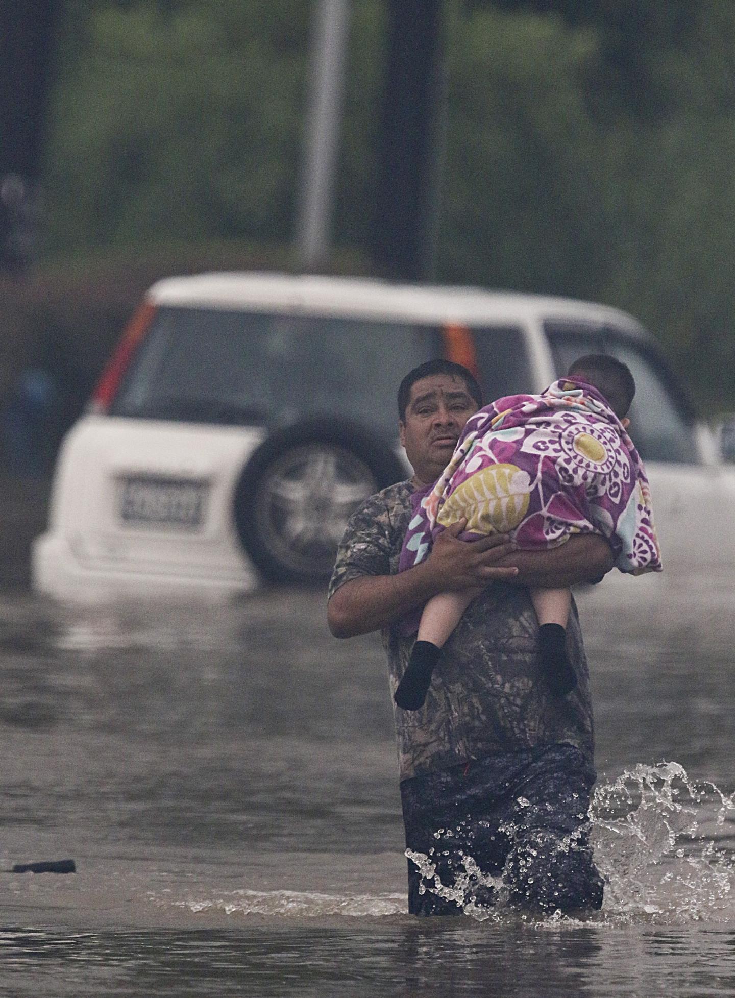 Un homme évacue un enfant.