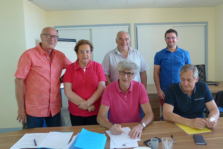 Antoine Faure, maire d'Aups, appose sa signature sur le premier dossier, Bernard Pantel à droite. Au 2e rang, Jean Bacci, Raymonde Carletti, Rolland Balbis et Loïc Imbard.
