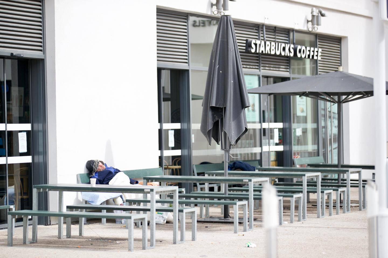 Sur le quai de la gare vide tous voyageurs, deux SDF ont transformé la terrasse du Starbucks (fermé) en dortoir... Moins de bruit alentour pour dormir, c'est toujours ça de gagné…