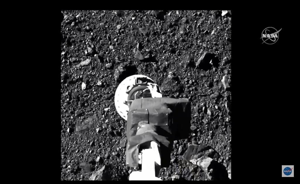 Cette image montre le bras de la sonde Osiris-Rex, pointée vers le sol de l'astéroïde, juste avant le contact, le 20 octobre 2020