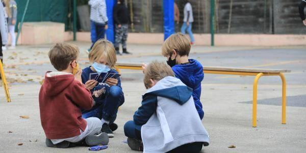 Des écoliers portant le masque lors d'une récréation. Illustration.