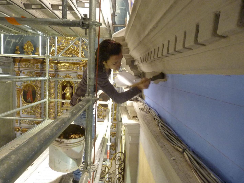 Dans la nef centrale, perchés sur un immense échafaudage, les fresquistes colorent les murs à la chaux. Dans le fond, le retable a été entièrement restauré.