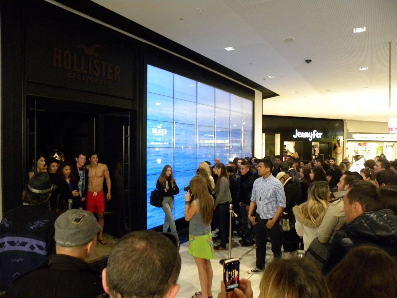 La foule était là, hier, devant le magasin Hollister, attirée par deux jeunes hommes aux torses nus et aux abdos bien dessinés.