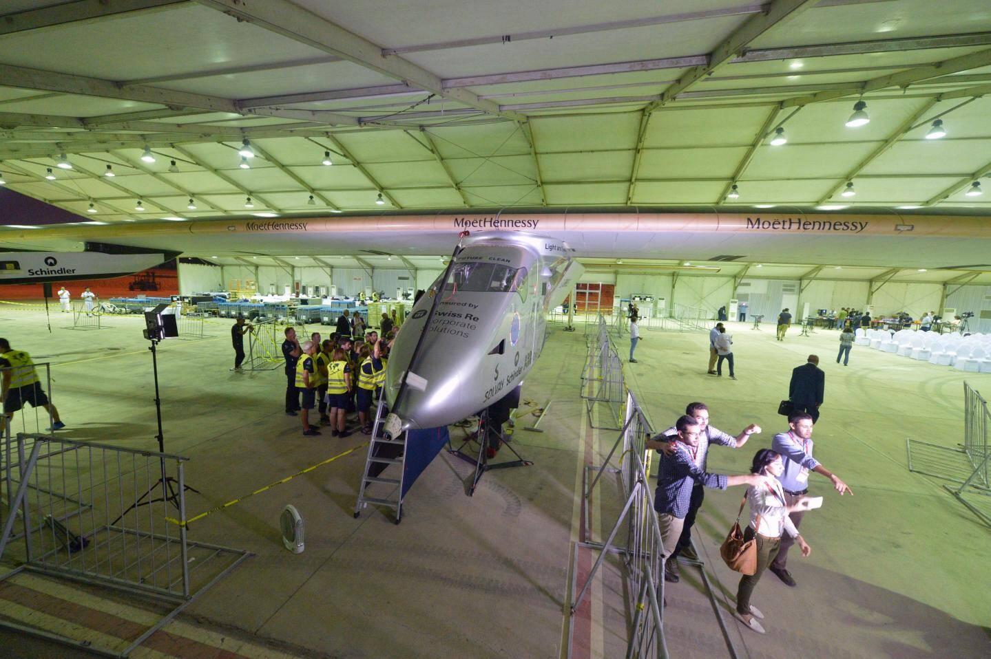 Des techniciens inspectent l'avion solaire à l'aéroport international du Caire.