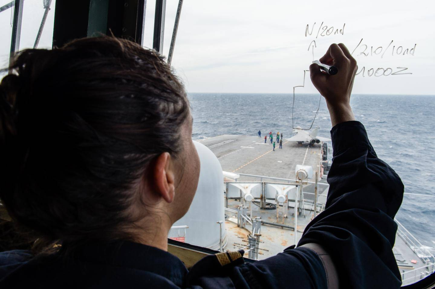 Un navigateur timonier note des informations sur la vitre de la passerelle du Porte-Avions Charles-de-Gaulle, le 9 septembre dernier, en mer méditerranée.