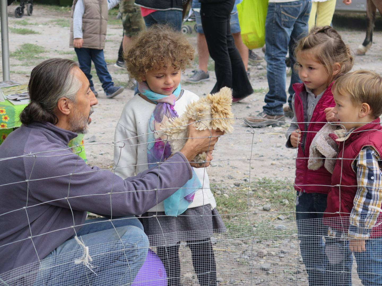 Des enfants en admiration devant une poule de la ferme Saveur-Caprine.