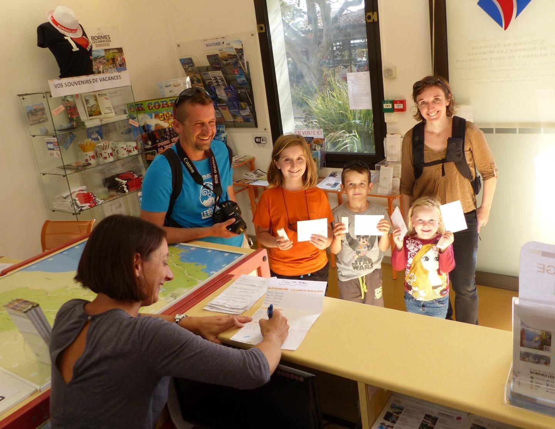 Les touristes participent en famille au quizz sur l'histoire locale en visitant le village médiéval.