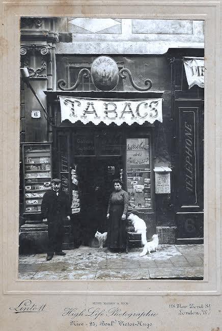 Mr et Mme Serramoglia et leurs chats sont devant leur magasin de tabac et de souvenirs à côté du pilastre à chapiteaux toujours visible au 15 rue de la préfecture.