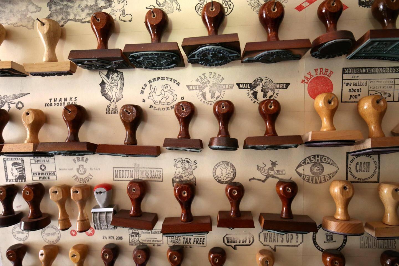 Une collection de tampons, réalisée sur mesure, couvre les murs de la demeure de l'artiste qui a, par ailleurs, conçu des timbres à son effigie (ci-dessous) qu'il mêle à de vrais timbres postaux au fil de ses envois.